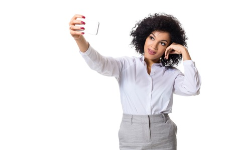 Beautiful brunette woman in classic white shirt and skirt make selfie on the phone. Stock Photo