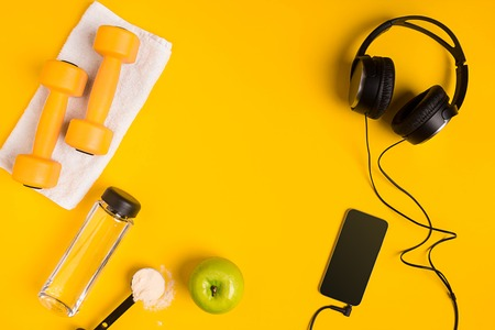Athletes set with female clothing, dumbbells and bottle of water on yellow background