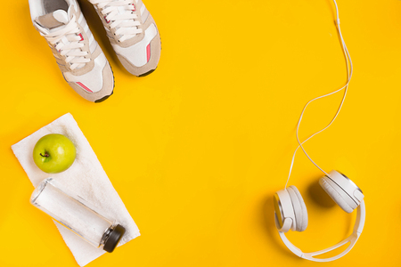 Athletes set with female clothing, headphones and bottle of water on yellow background