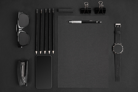 Blank notepad with clips, pens and glasses flat lay. Top view on set of black office supplies and spectacles, free space. Art, business, creation, imagination, education, stationery concept Stock Photo