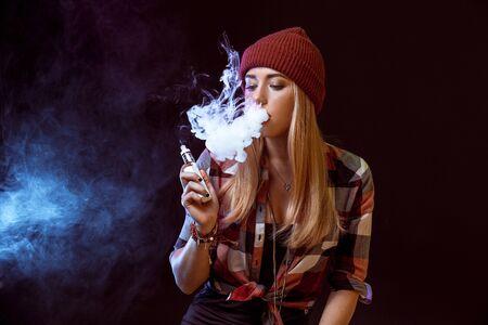young woman smoking electronic cigarette 版權商用圖片