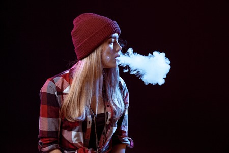 young woman smoking electronic cigarette Stock Photo