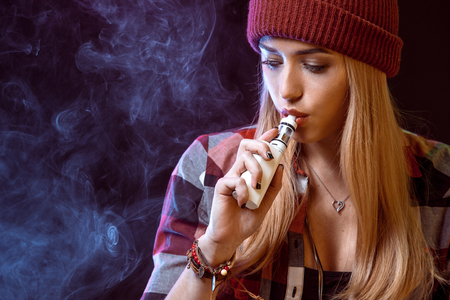 young woman smoking electronic cigarette Standard-Bild