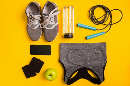 Fitness accessories on a yellow background. Sneakers, bottle of water, apple and sport top.