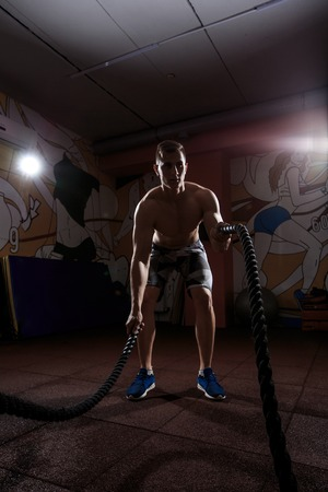 battling: Young man working out with battle ropes at crossfit gym