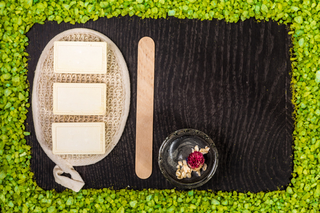 spa products: black mud and clay powder, soap, bath salt on black wood table background. Still life. Top view. Copy space