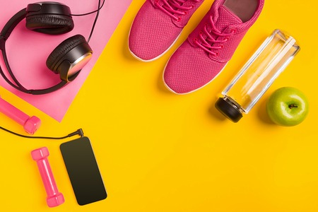 Fitness accessories on yellow background. Sneakers, bottle of water, headphones and smart. Stock Photo