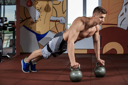 Man doing push-up exercise with dumbbell Stock Photo