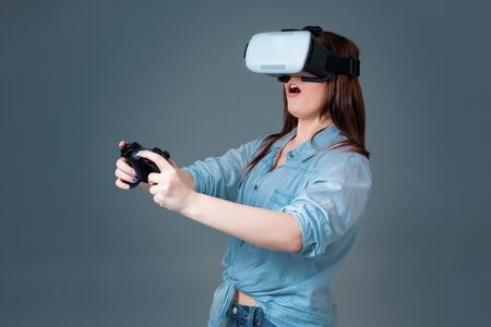 visualizing: Emotional young woman using a VR headset and experiencing virtual reality on grey background