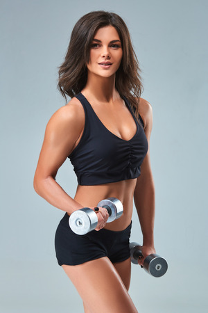 Athletic woman pumping up muscles with dumbbells on gray background