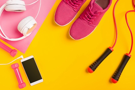 clothe: Fitness accessories on yellow background. Sneakers, dumbbells, headphones and smart. Stock Photo