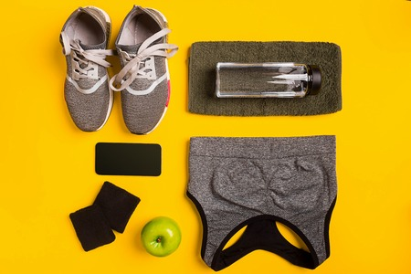 Fitness accessories on a yellow background. Sneakers, bottle of water, smart, towel and sport top.