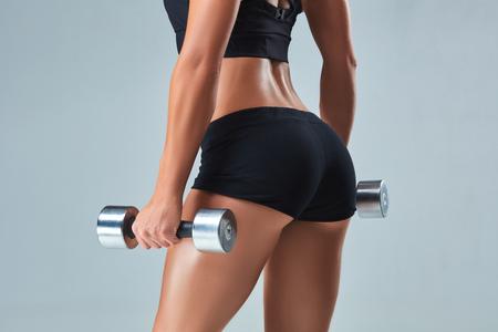 Athletic donna pompare i muscoli con manubri su sfondo grigio
