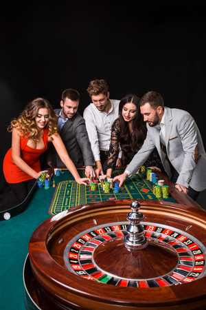 gambler: Group of young people behind roulette table on black background Stock Photo