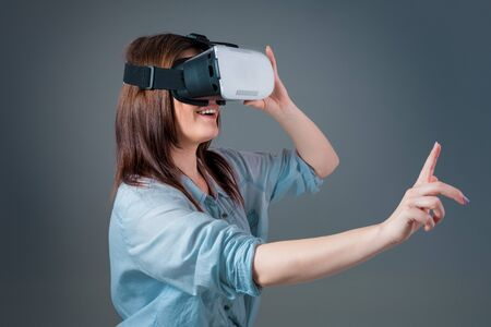 Emotional young woman using a VR headset and experiencing virtual reality on grey background Banco de Imagens