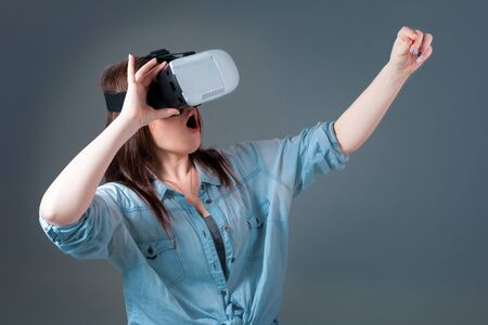 Emotional young woman using a VR headset and experiencing virtual reality on grey background