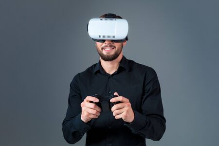 Emotional young man using a VR headset and experiencing virtual reality on grey background