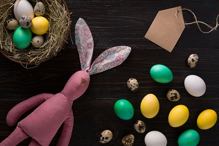 huevos de codorniz: Easter eggs in nest and pink rabbit on a black background