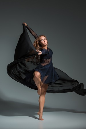 belles jambes: Dancing woman in a black dress. Contemporary modern dance on a gray background.