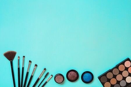 Various cosmetics and brushes on blue background. Top view. Still life. Copy space