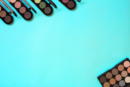 Various eyeshadow on blue background. Top view. Still life. Copy space