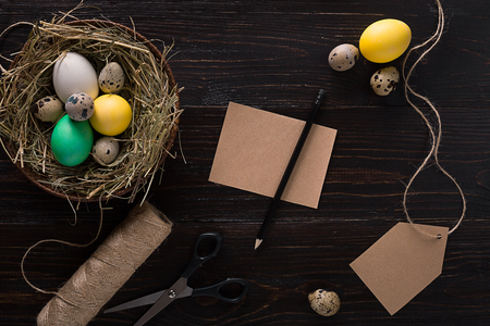 Colorful easter egg in nest on dark wood board. Stock Photo