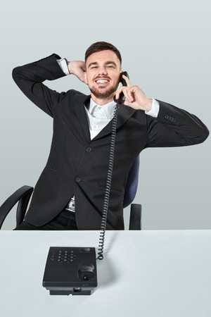 biz: young man dials the phone number while sitting in the office
