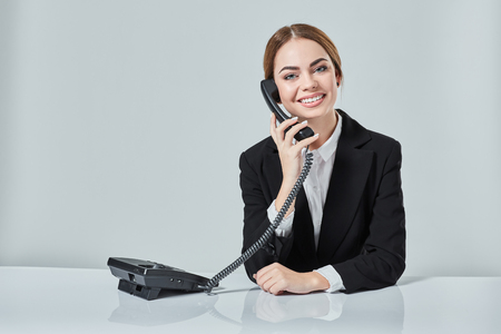 attractive dark-haired woman dressed in a black suit is sitting at  table in an office. Stock Photo