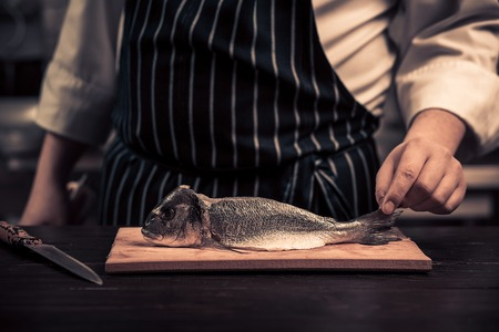 stewing: Chef cutting the fish on a board. Photo in brown tones. Kitchen. Wooden table