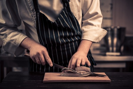 stewing: Chef cutting the fish on a board