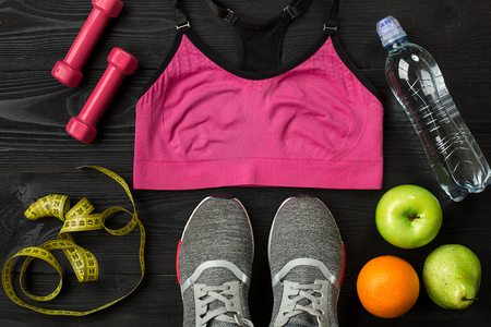 Workout plan with fitness food and sport equipment on dark background, top view. Copy space. Still life
