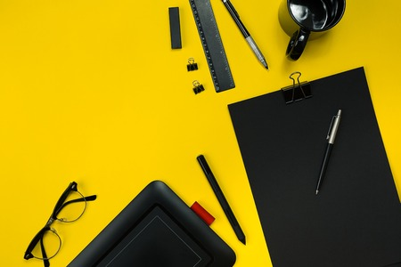 Flat lay display of business office gadgets with notepad, cup, pen, develop, glasses and etc. Top view display with copy space for display anything into images. Black office objects on a yellow background Stock Photo