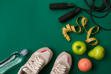 Workout plan with fitness food and sport equipment on green background, top view. Copy space. Still life