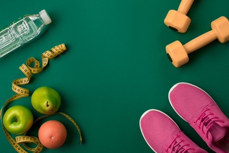 Athletes set with female clothing and bottle of water on green background Stok Fotoğraf - 75356051