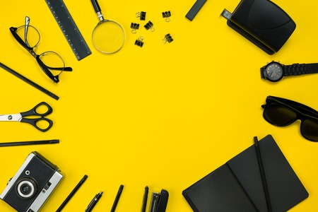 Black objects from the office on a yellow background. Work and creativity. Top view.