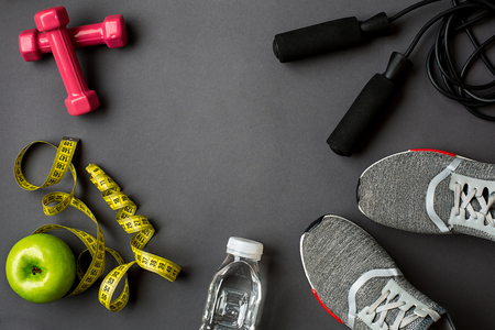 Athletes set with female clothing, sneakers and bottle of water on gray background