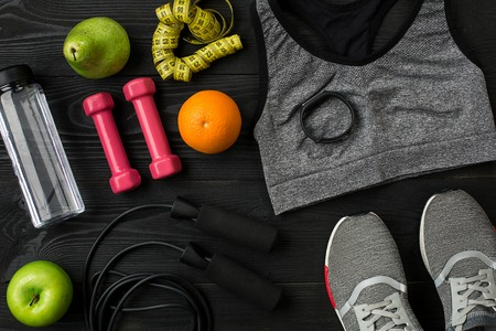 stuff: Athletes set with female clothing, sneakers and bottle of water on dark background