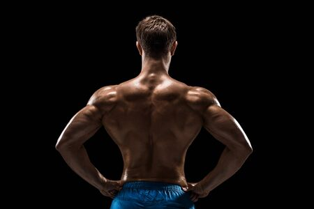 Strong Athletic Man Fitness Model posing back muscles, triceps over black background