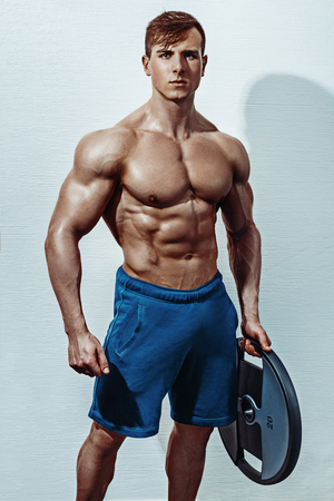 Male bodybuilder, fitness model trains in the gym. Handsome male athlete in shorts with a beautiful body Stock Photo