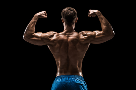 suntanned: Strong Athletic Man Fitness Model posing back muscles, triceps over black background