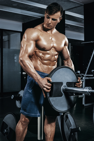 retouched: Male bodybuilder, fitness model trains in the gym Stock Photo