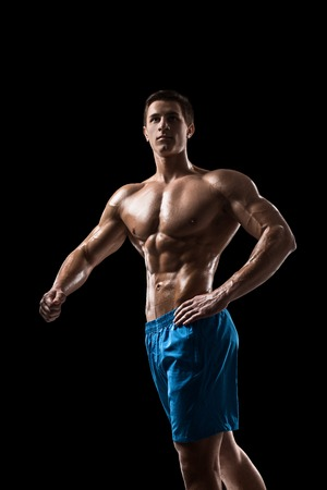 Muscular and fit young bodybuilder fitness male model posing over black background. Stock Photo