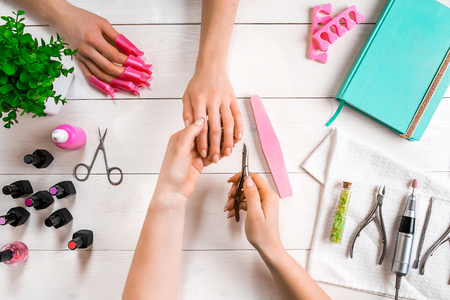 Manicure for the client. Close-up of the hands of a manicurist and client on a wooden background