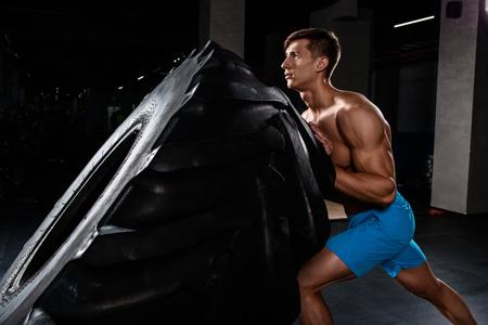 Crossfit training - man flipping tire in gym