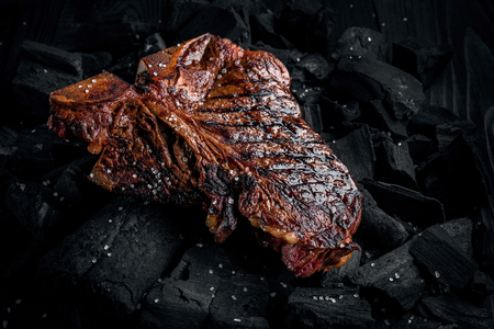 Grilling a tasty tender marinated t-bone steak on a coals. Close up view