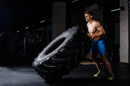 pushes: training - man flipping tire in gym. A muscular man pushes a big tire