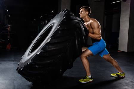 training - man flipping tire in gym. A muscular man pushes a big tire
