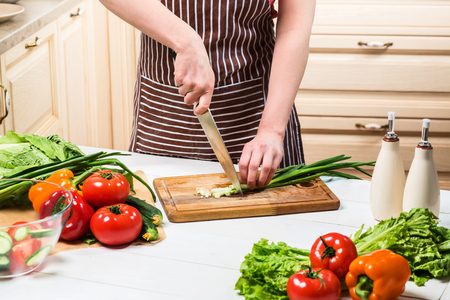 Young woman cooking in the kitchen at home. A woman cuts a green onion and vegetables with a knife. Stock Photo