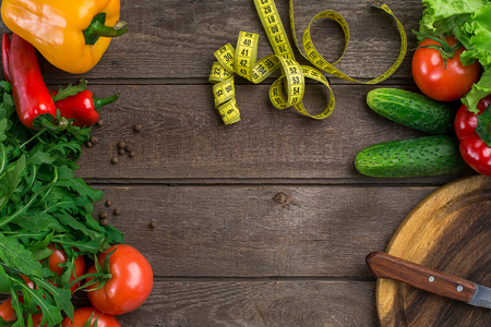 Vegetables and in measure tape in diet on wooden background. Top view. Stock Photo