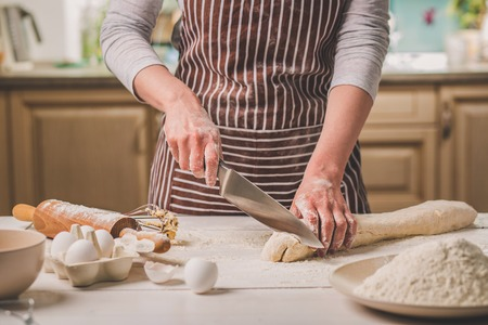woman's hands: Close-up view of two womans hands cut knife dough